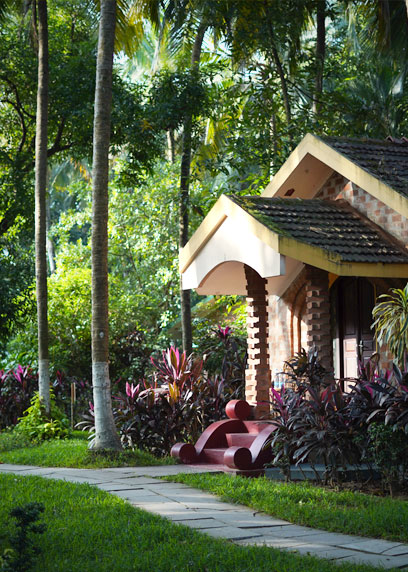 Entrance of the Royal Villa surrounded by lush green palm trees | Kairali-The Ayurvedic Healing Village